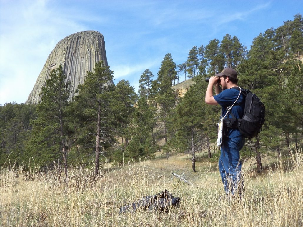 Jake Hourt conducts an IMBCR point count in the shadow of Devil's Tower in 2014. Photo by Nick Van Lanen.