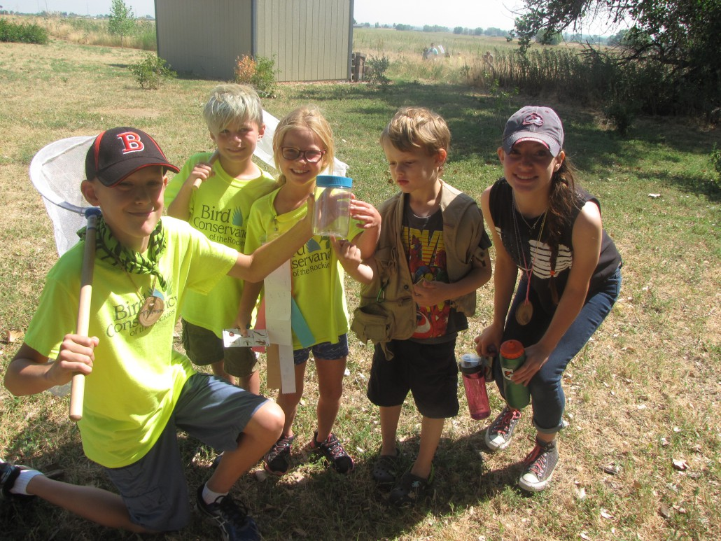 Nature Investigators Day Campers showing off their bugs with two LIT's.
