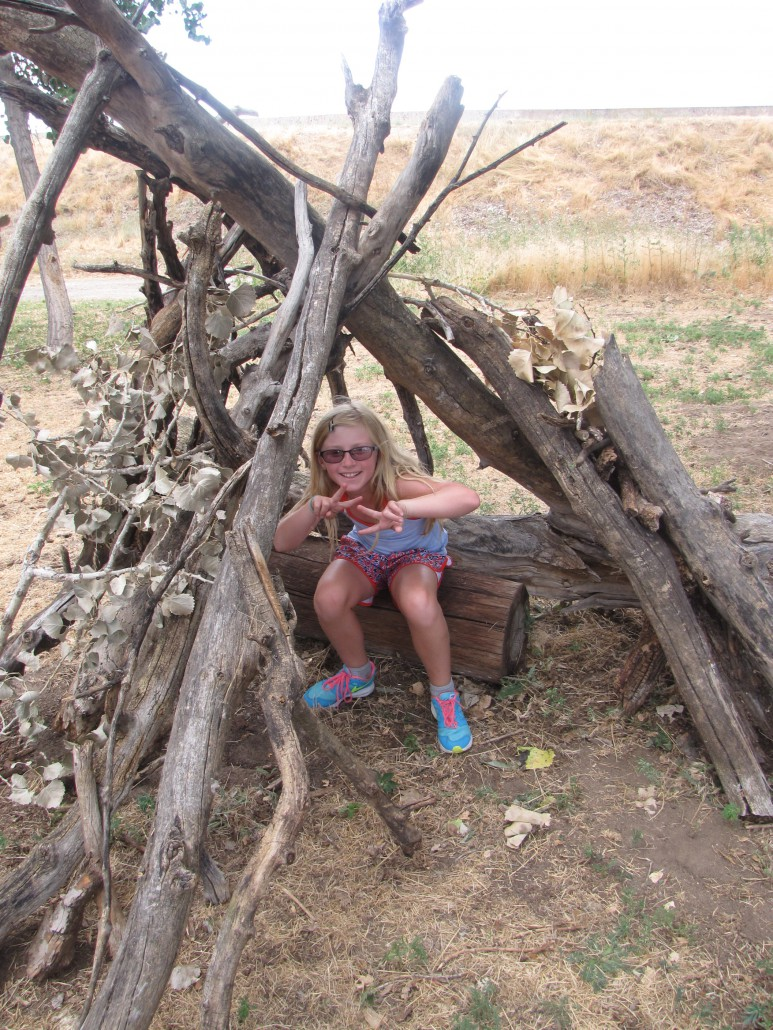 Sky and Earth Day Camper in a fort that they built at the Old Stone House while learning about habitat.